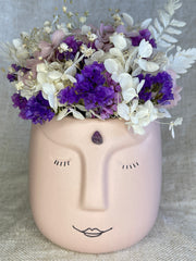 Preserved flowers in a face vase