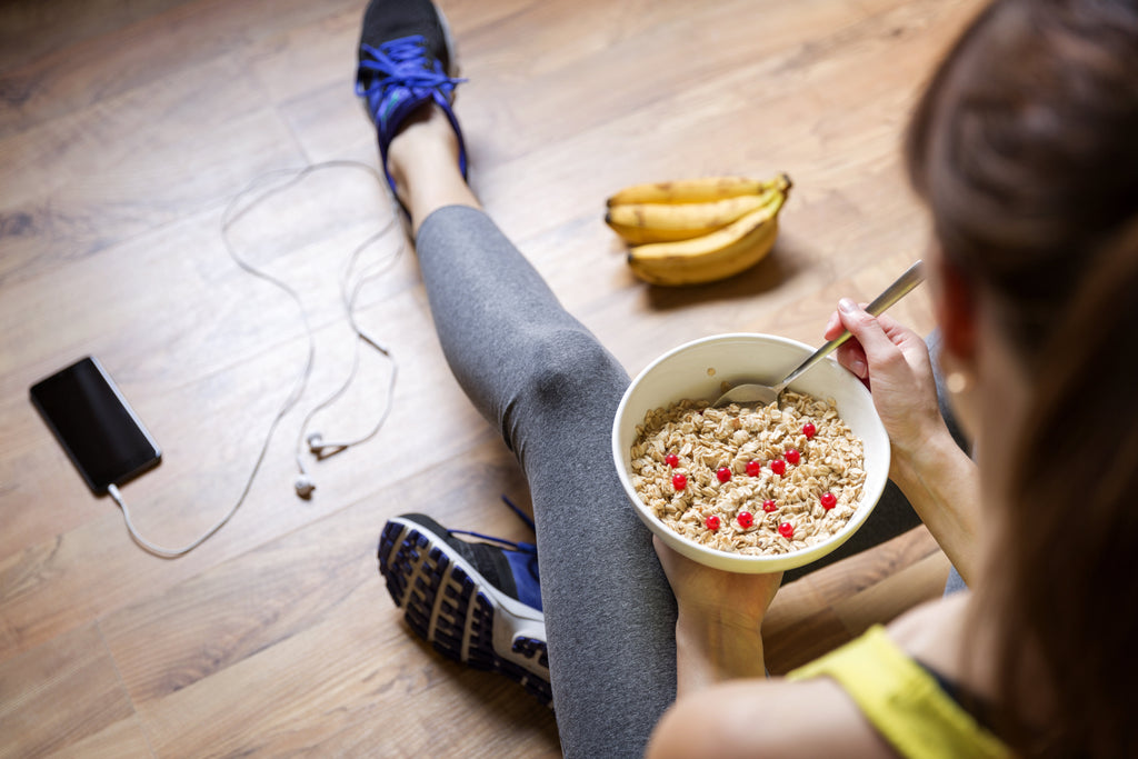 Healthy woman eats oatmeal with berries and bananas after exercising