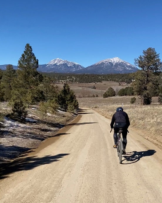 bicycle rider on a dirt road with mountains in the background