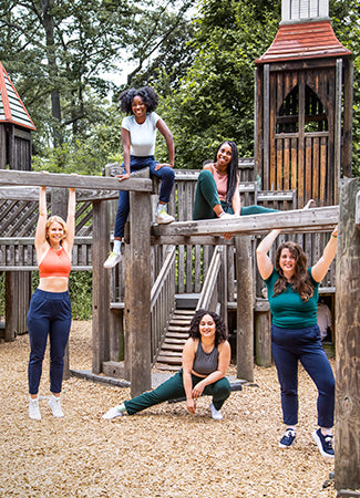 five diverse women wearing forest green open-air pants and navy open-air pants by alder apparel in high park, toronto