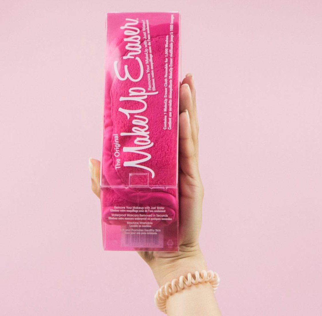 Hand holding up pink MakeUp Eraser box