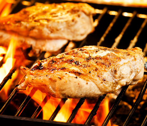 Chickenbreast on a grill lightly brown with a crust