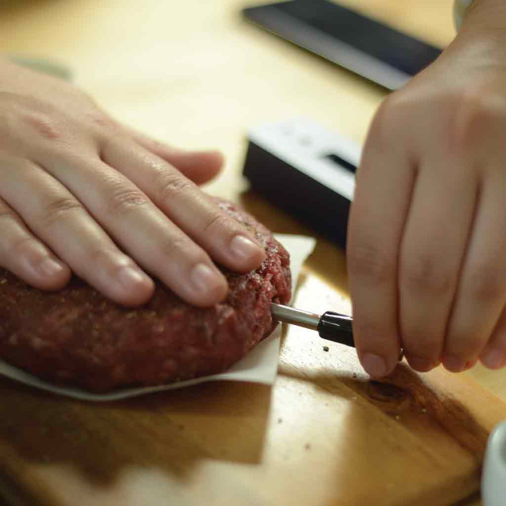 The Meatstick is being inserted into a burger
