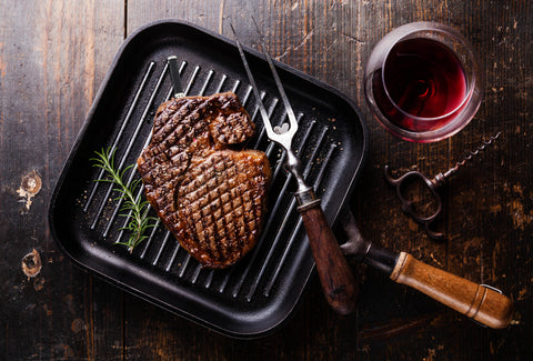 Ribeye Steak with Rosemary in a pan. Surrounded by a glass of red whine and a grilling fork.