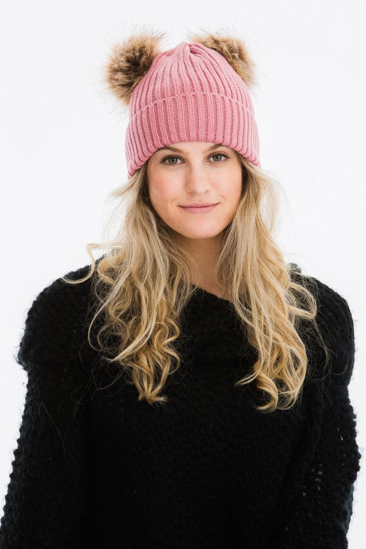 blush pink winter hat with 2 pom poms attached