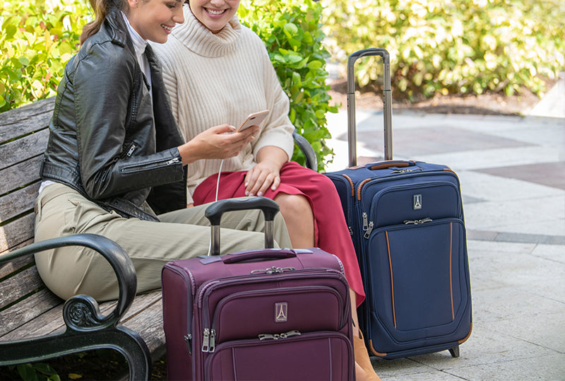 two women sitting on bench with two travelpro suitcases