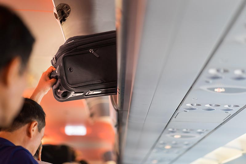 carry-on luggage being placed in a aircraft overhead bin