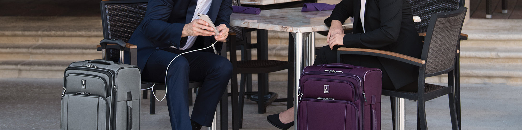 Two people sitting down charging their phone in the USB port on their luggage