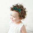 curly haired toddler wearing olivia headband with emerald green lace bow