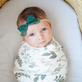 newborn photography greenery swaddle and green bow headband baby bassinet