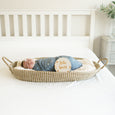 baby in bassinet with hello world star motif sign