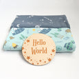 moon and stars nursery with camping and night sky swaddles and hello world engraved sign
