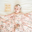 baby girl with custom daisy name sign and peach posey swaddle blanket