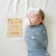 baby girl with custom wooden name sign, bibs, pacifier, blue stars blanket