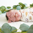 baby in eucalyptus wrapped in safari animals swaddle wearing stretchy headband pink lace bow