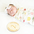 baby with 2 month age growth milestone sign disc round swaddle and bow