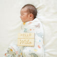 baby in underwater swaddle with name badge style sign hello my name is