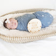 baby in basinet with swaddle, bow, and star name sign