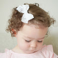 Little girl with white bow clip Village Baby Charlotte Lace