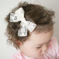little girl wearing Abigal village baby lace bow in curly hair