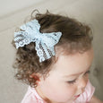 toddler girl with light blue Reese lace clip in bow