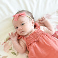 baby girl in dusty orange coral outfit with lace bow