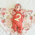 cute baby girl with number two sign because she is two months old with floral swaddle knit blanket