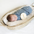 baby in starry dreams swaddle in basket with number one wooden sign