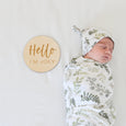 baby in graceful greenery blanket and hat set with custom name sign