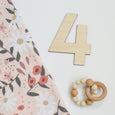 peach posey swaddle blanket with number four bold cutout milestone and rattle