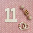 number eleven with wooden rattles on 1st colored blanket for baby