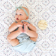 baby with twelve month milestone sign pattern blanket lace headband photography
