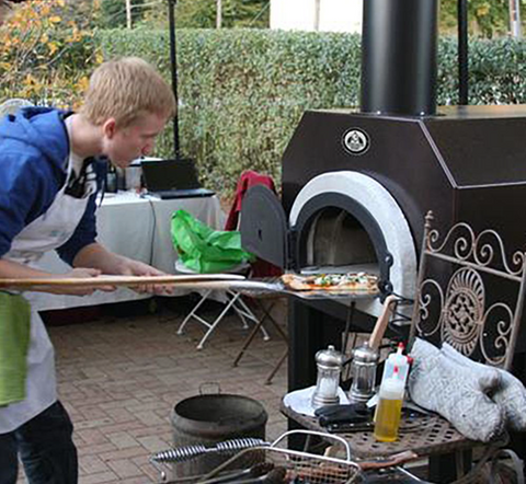 Image of Chicago Brick Oven - CBO-500 - Pizza Oven - Lifestyle image man removing pizza