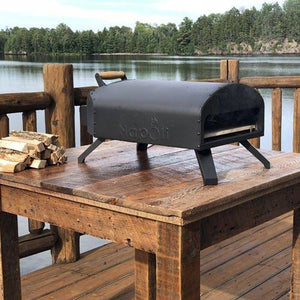Napoli Bertello Portable Outdoor Pizza Oven on table at lake