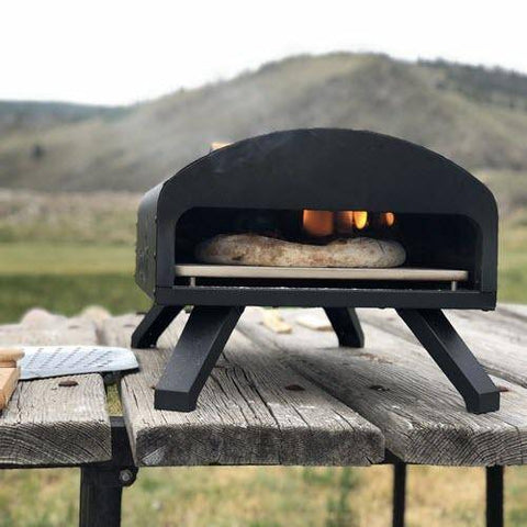 Image of Napoli Bertello Portable Pizza Oven on table with mountains in the background