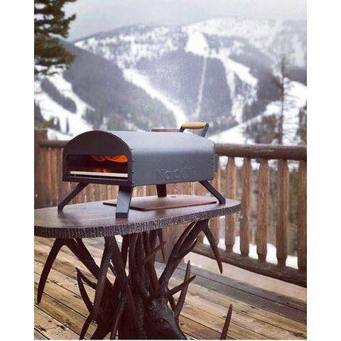 Image of Napoli Bertello Portable Pizza Oven on table in front of snow covered mountains
