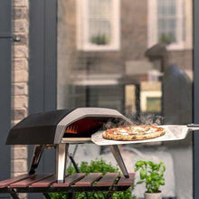 Ooni Koda portable propane pizza oven cooking pizza on a balcony