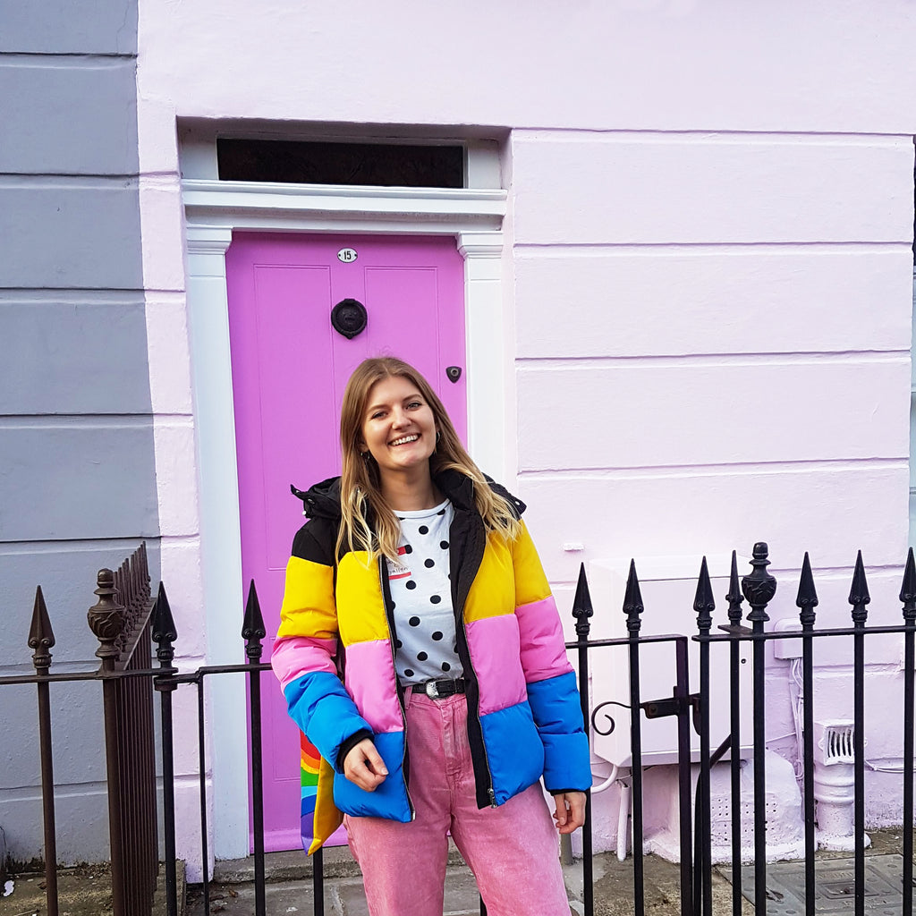 Zabby Allen wearing a pink, yellow and blue jacket, pink jeans a a polkadot t-shirt in front of a pink door in Camden, London