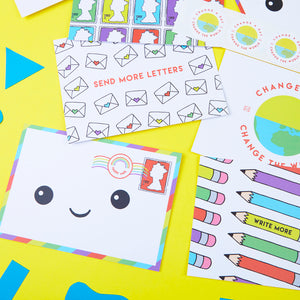 Postcard Set Featuring a stamp pattern, a kawaii smiling envelope, send more letters postcard with envelope pattern, write more postcard with pencil pattern and a Change a Day Change the World logo postcard