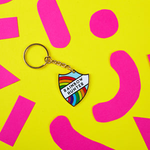 "A luxury enamel key chain in a merit badge style featuring a rainbow and the text ""Rainbow Hunter"" by Zabby Allen"
