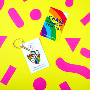 "A luxury enamel key chain in a merit badge style featuring a rainbow and the text ""Rainbow Hunter"" by Zabby Allen. Shown with a backing card saying 'Chase Rainbows Every Day'"