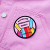 Dungaree Appreciation Society Patch showing rainbow dungarees on a pink background with black text designed by Zabby Allen in collaboration with Lucy & Yak