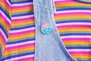 Dungaree Appreciation Society enamel pin on denim dungarees and a rainbow striped t-shirt