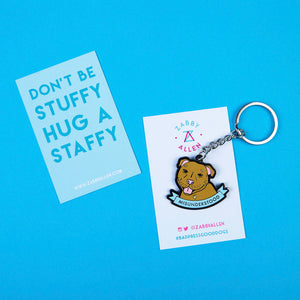 "Keyring featuring a Staffordshire Bull Terrier Graphic Illustration and a scroll reading Misunderstood - design by Zabby Allen - on backing card that reads ""Don't Be Stuffy, Hug a staffy"""