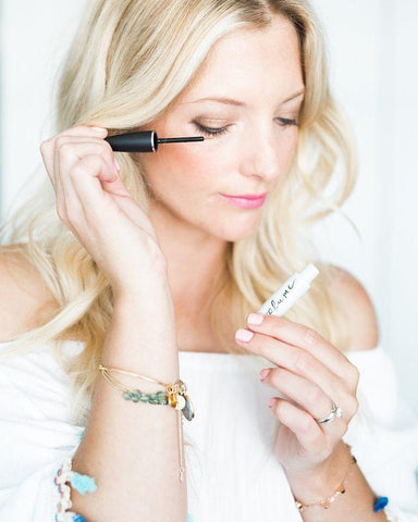 woman applying Plume eye lash serum