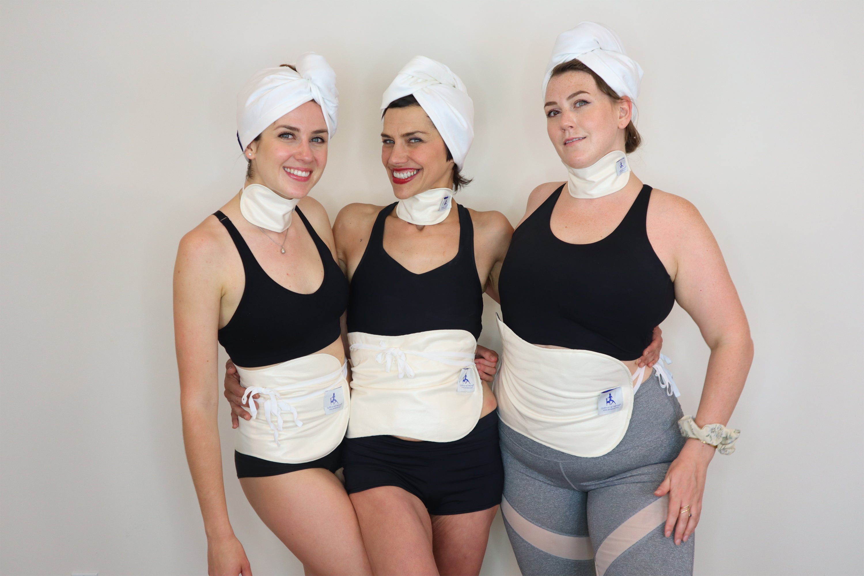 Dr Marisol and two other woman smiling wearing the castor oil packs