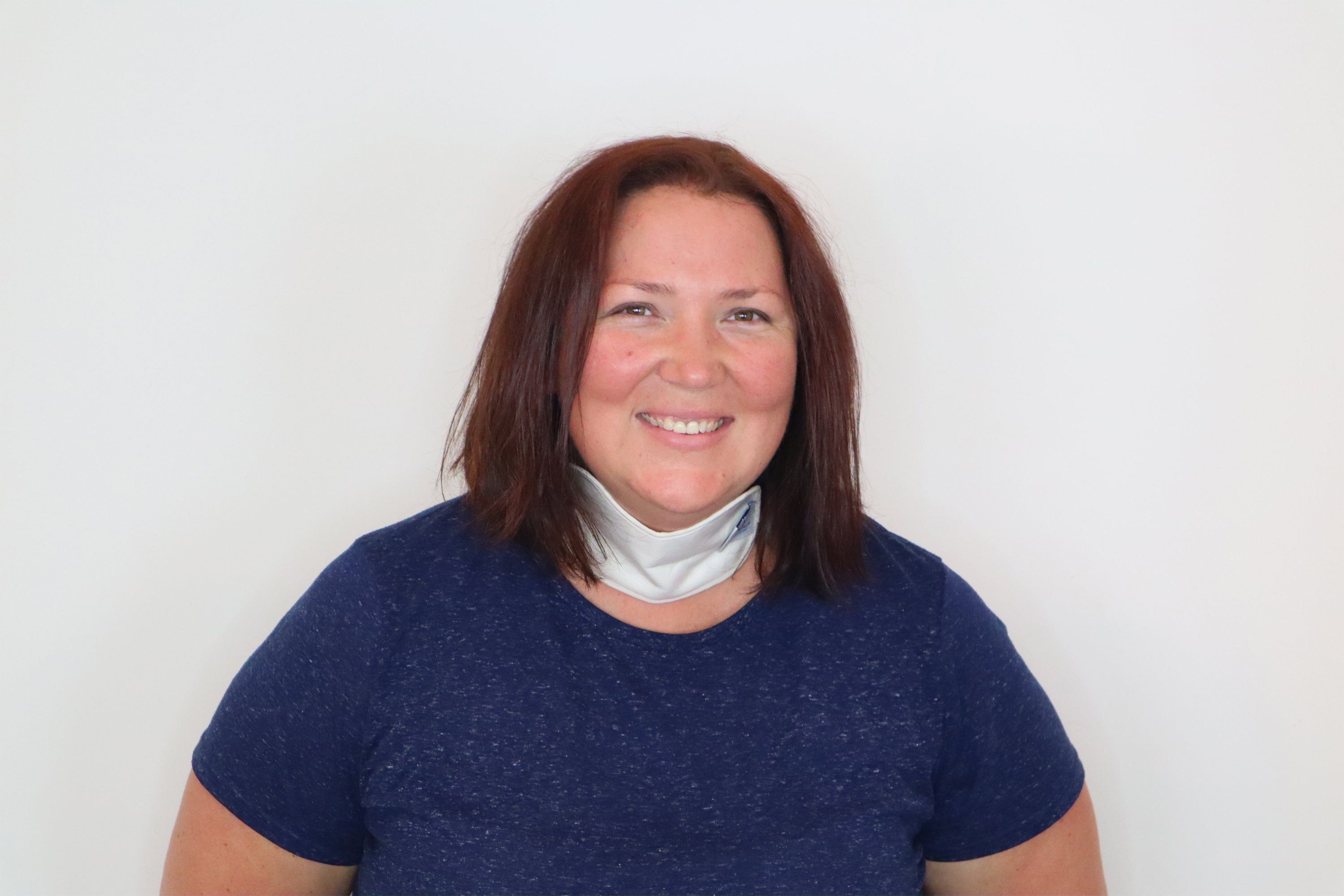 A woman smiling wearing the thyroid pack