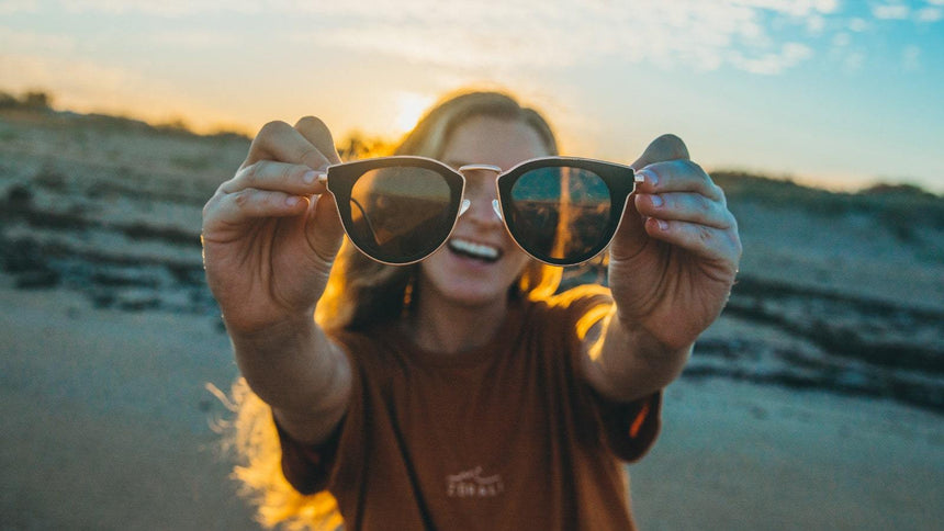 Women holding a pair of wooden sunglasses up on a beach during a sunset | Vilo Eyewear Australia