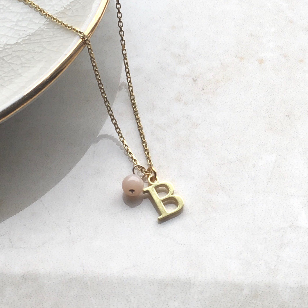 gold initial charm necklace with pink opal birthstone