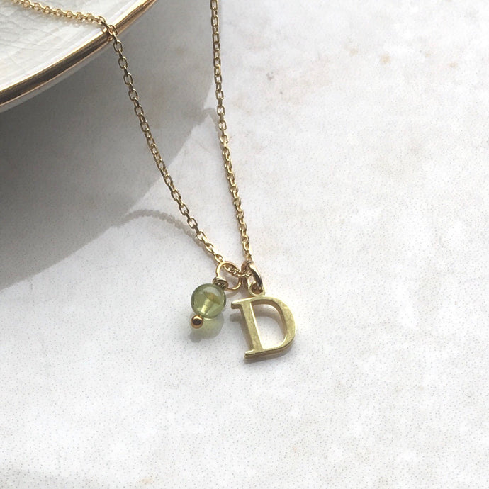 gold initial charm necklace with peridot birthstone